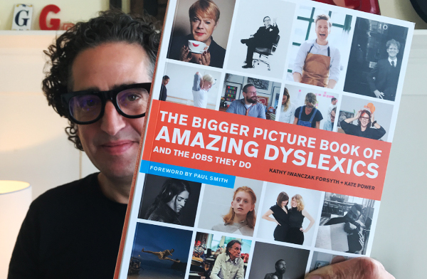 Gil Gershoni is holding a copy of The Bigger Picture Book of Amazing Dyslexics and the Jobs They Do.