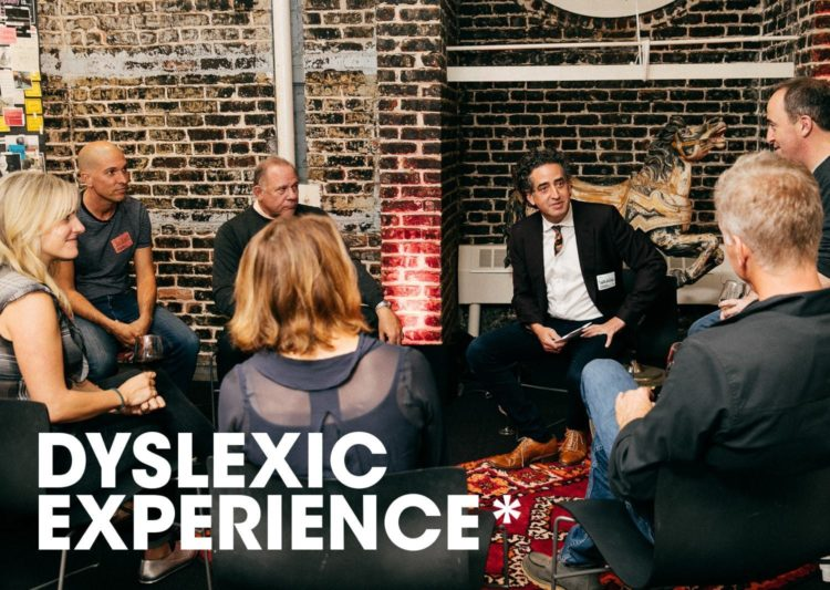Gil Gershoni seated, surrounded by six people in conversation. The Dyslexic Experience logo is in the lower corner.