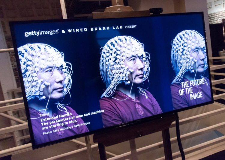 A television screen with 3 identical photos of a man wearing an EEG cap used for measuring brain waves.
