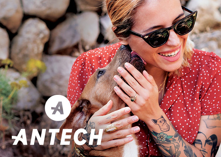 Brown dog licks a blonde, tattooed woman on the ear. White Antech logo is in the lower left corner.