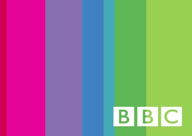 The BBC logo superimposed over a background of purple, pink, green and blue vertical stripes.