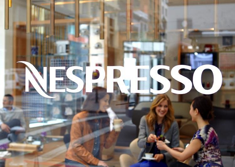 A group of women is seated inside a Nespresso coffee shop. The white Nespresso logo is superimposed on the image.
