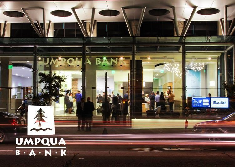 Umpqua Bank photographed from the outside. The building's facade is made entirely of glass.