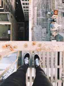 Photo of a set of legs standing on a fire escape, looking down at the buildings below.