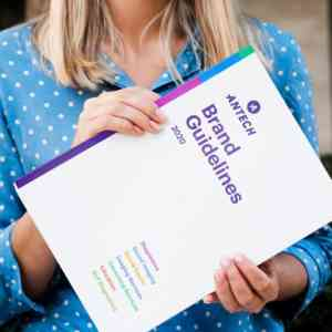 A blonde, white woman holds a copy of Antech's brand guidelines. It is a white booklet with purple lettering.