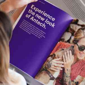 A woman looks at Antech's brand guidelines. The booklet is opened to a purple page explaining Antech's visual rebrand.
