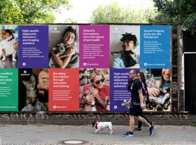 A couple walks a small white dog in front of a series of posters advertising Antech's services.