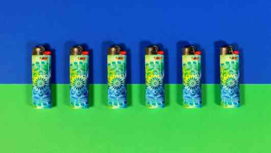 Six blue and green Bic lighters skinned with a psychedelic pattern staged on a blue and green background.