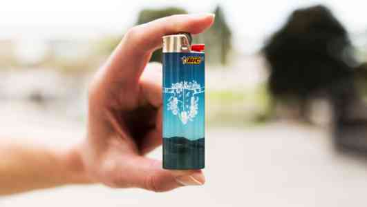 A light-skinned hand holds up a blue Bic lighter in front of a blurry background.
