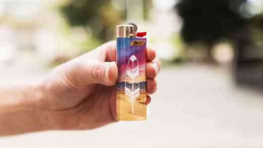 A light-skinned hand holds up a Bic lighter skinned with a photo of a sunset and an illustration of a feather.