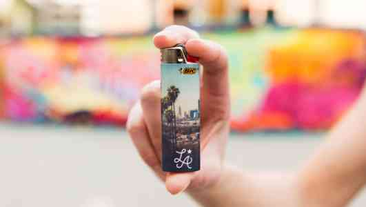 A light-skinned hand holds up a Bic lighter skinned with a photo of Los Angeles.