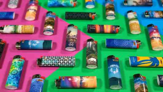 Bic lighters arranged in a tessellation on top of a pink, green, and blue background