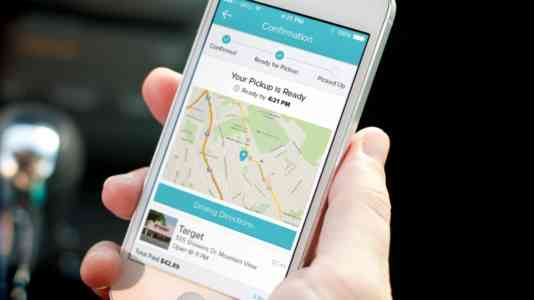 A hand holds a cellphone opened to the Curbside mobile app. The app indicates an order is ready for pick-up.