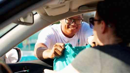A person in a white shirt leans through a car window to hand someone a blue bag.