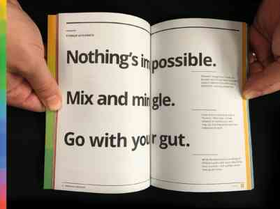 "Two hands open the field guide to a page that reads, ""Nothing's impossible. Mix and mingle. Go with your gut."""