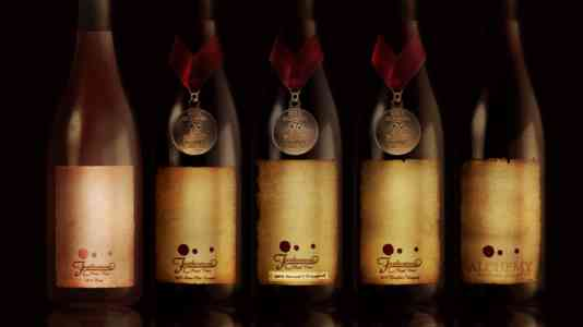 Five bottles of Furthermore wine staged on a dark background.