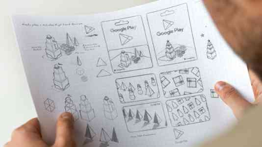 A person looks at a series of sketches for an animation featuring the Google play gift card.