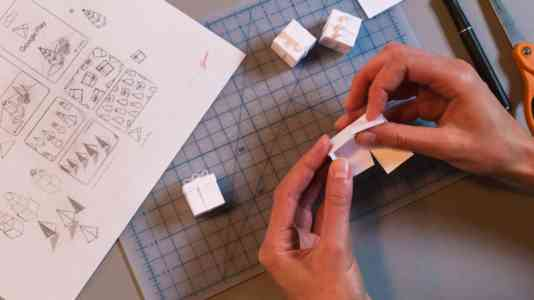 Two hands fold a piece of paper into an origami gift box. To the left are sketches for an animation.