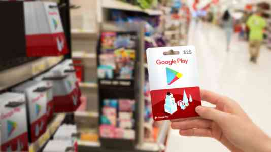 A light-skinned hand holds a Google Play gift card in a grocery store.