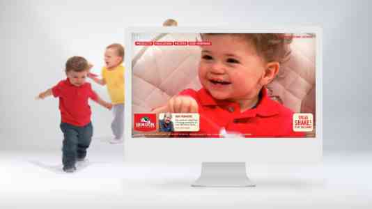 Two toddlers run behind a computer monitor. The computer is opened to the Horizon website and a photo of a toddler.