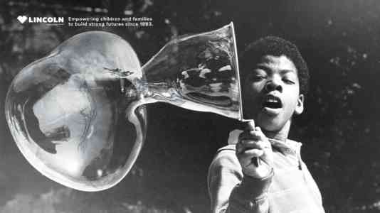"""A child uses a bubble wand to blow a large bubble. At the top, it reads, """"Empowering children and families to build strong futures since 1883."""""""