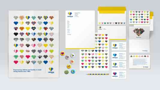 Overhead shot of various assets created for Lincoln, including a pamphlet, business cards, letterhead and buttons.
