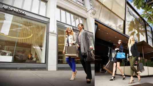 Four stylish women walk past a Nespresso café.