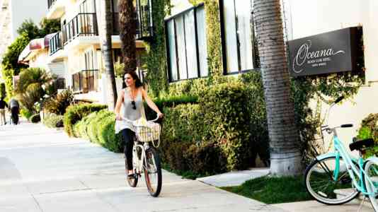 A woman on a bicycle rides past the Oceana Beach Club Hotel.
