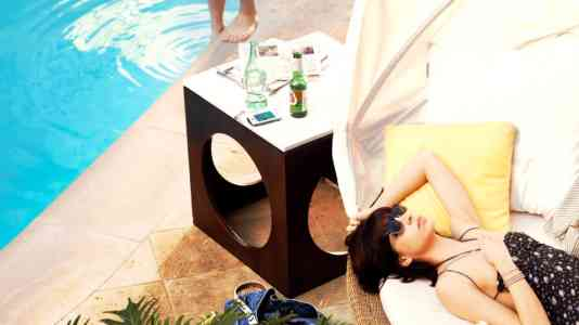 A brunette woman lounges poolside on a white chair. The Oceana Beach Club Hotel logo is in the lower right corner.