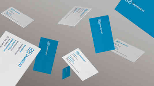 Mock-up of SharesPost business cards falling through the air. They have one blue side and one white side.