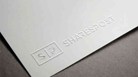Close-up of the SharesPost logo embossed on a white piece of paper.