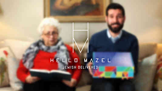 Out-of-focus photo of a young man and an old woman holding the Hello Mazel box. The brand logo is superimposed over the photo.