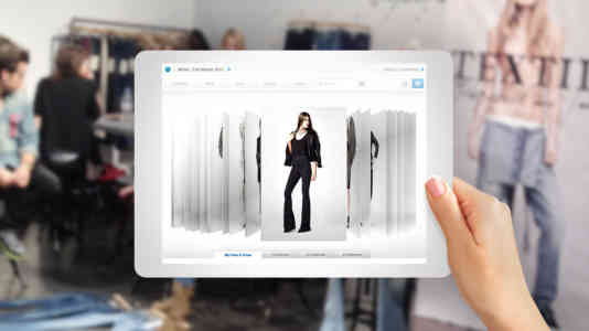 Out-of-focus photo of a fashion designer's studio. In the foreground is a person holding a tablet opened to the Threadsuite website.