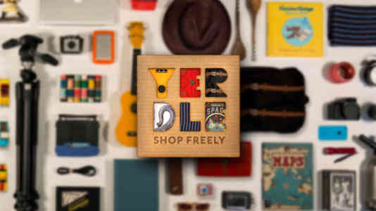 Out-of-focus photo of an assortment of items, including a tripod, a ukulele and a camera. The Yerdle logo is superimposed over the photo.
